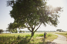 couple holding hands under a tree