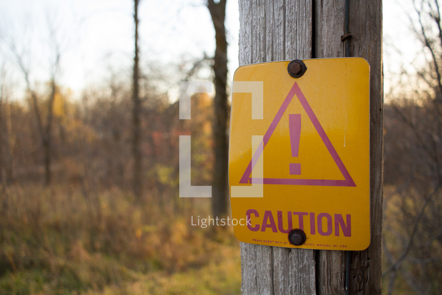 caution sign on a wood post