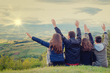 Christian worship and praise. Group of friends hugging outdoors at sunset.