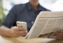 a man looking at his cellphone and reading a newspaper