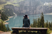 Woman sitting on a bench at a mountain lake