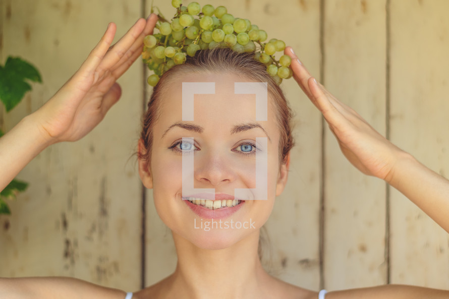 a woman with grapes on her head