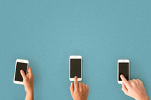 Three hands with cell phones lined up on a blue surface.