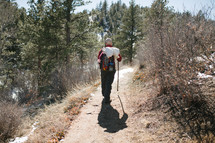 man with a walking stick on a nature trail