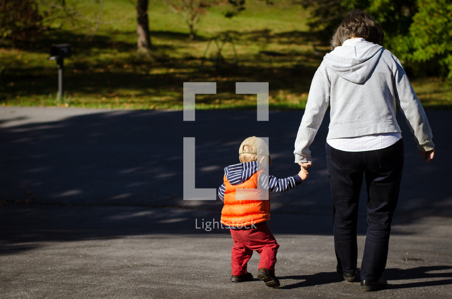 a grandson and grandmother walking holding hands