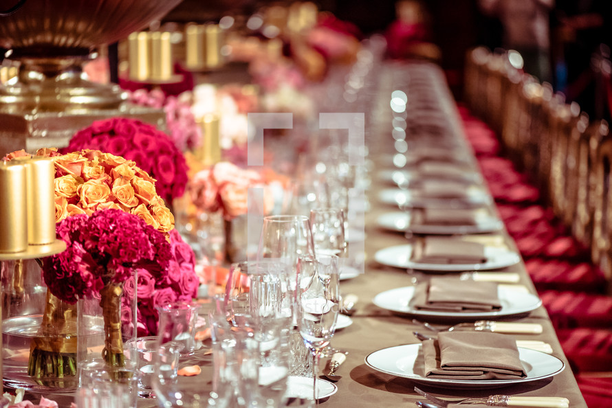 a banquet table with place settings and centerpieces