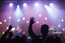 silhouettes of raised hands in an audience at a concert