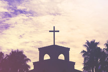 silhouette of a cross on a church roof