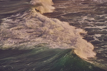 Big wave crashing through the ocean during early morning sunrise