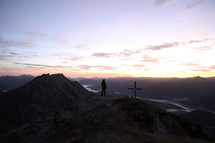 cross and silhouette of a man on a mountain top at sunset