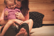 a mother hugging her toddler daughter