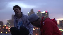 young men sitting on a roof talking above a city