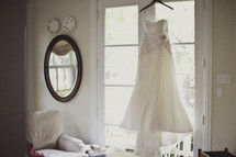 Bridal gown hanging in a window