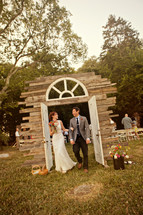 bride and groom walking through doorway arch