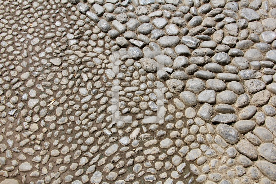 Stone pebbles texture on paved pathway