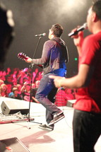 man playing guitar and singing on stage