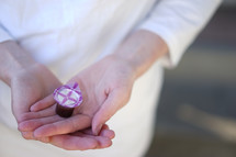 cupped hands holding a travel communion cup