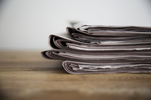 stack of newspapers on a wood table.