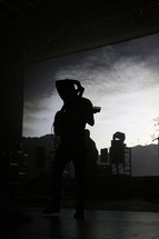 silhouette of a man on stage putting his guitar over his shoulder