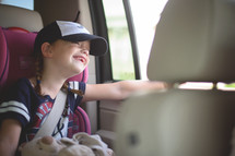 a little girl riding in a car seat
