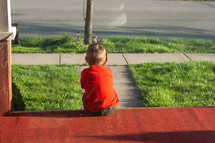child sitting alone on a front porch waiting