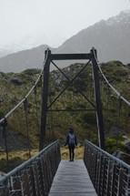 a woman walking across a bridge