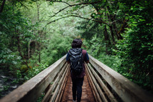Man walking over a bridge with a bagpack.