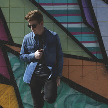 A young man standing in front of a geometric design on a wall