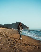 a young woman walking on a beach