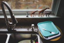 dirty dishes in a sink and plastic toy animals in a window sill