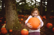 a girl child holding a pumpkin in a pumpkin patch
