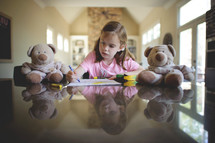 a little girl coloring with crayons and teddy bears