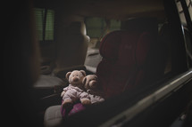 teddy bears in a booster seat in a car