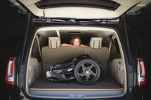 a child looking over the backseat and a stroller in the trunk of an SUV