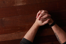 Adult male hands folded in prayer on a wooden background. Visible tattoo on forearm.