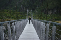 a woman walking across a swinging bridge