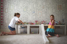 girls playing with legos in a playroom