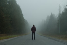 a woman standing on a foggy road