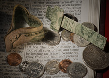 "Paper money heart and cross with coins on pages of Bible open to 1 Timothy 6:10 -- ""for the love of money."""