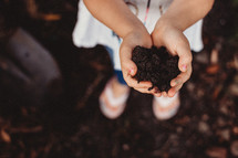 child with cupped hands with soil