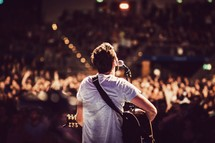 man singing into a microphone at a concert