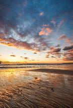 wet sand on a beach at sunset