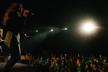 A singer on stage singing to a crowd of young people.
