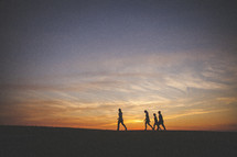 silhouettes of a family waling