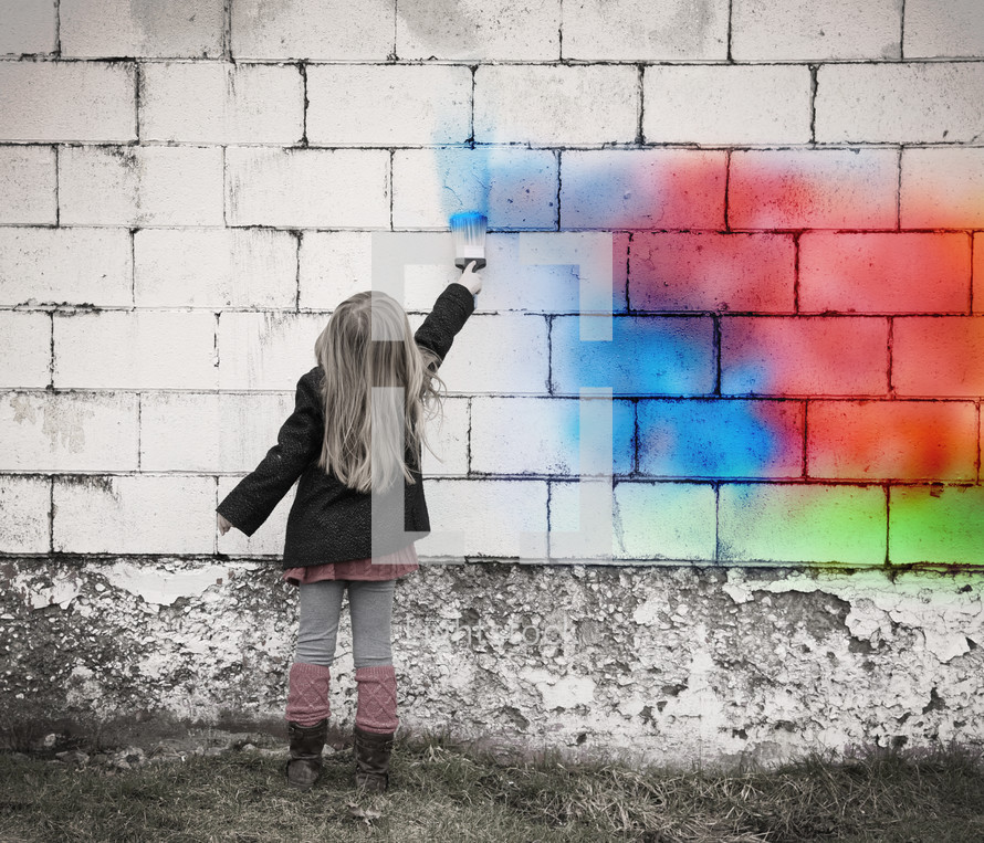 a girl child painting a rainbow on a wall