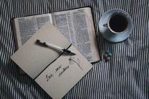 Love one another written in the pages of a journal and an open Bible