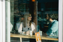Window view of a couple having coffee in a coffee shop.
