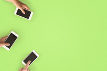 Three hands with cell phones on the left side of a green surface.