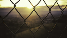 Sunrise through a chain link fence.