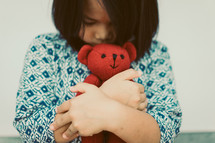 toddler hugging a teddy bear